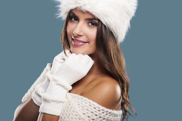 красивая девушка в белой шапке и перчатках на синем фоне
