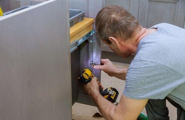 мужчина ремонтирует кухонную тумбу