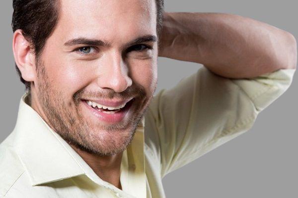мужчина с красивой улыбкой на сером фоне
