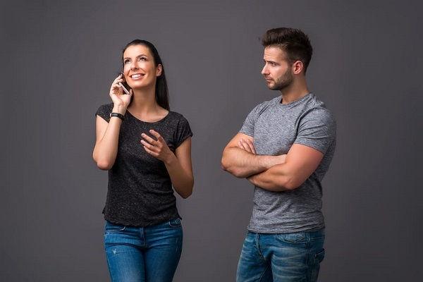 девушка провоцирует парня, разговаривая по телефону, чтобы он ревновал