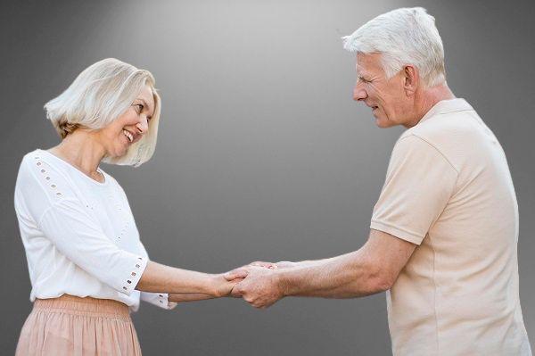 пожилая пара держат друг друга за руки