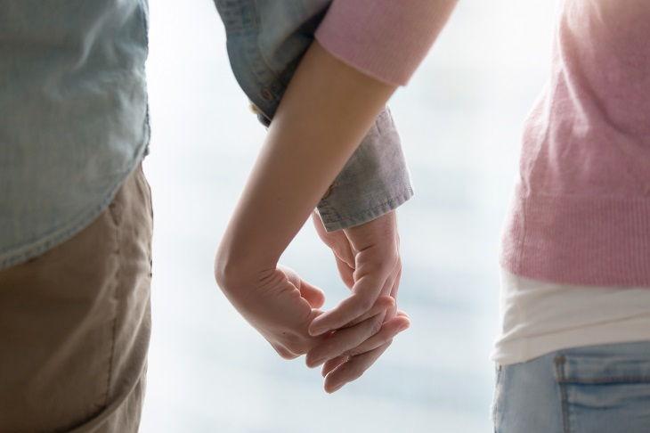 У женщины хорошие отношения с мужем, они любят держать друг друга за руки.