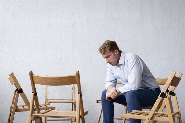 Мужчина переживающий кризис середины жизни сидит в одиночестве на сеансе групповой терапии с пустыми стульями.
