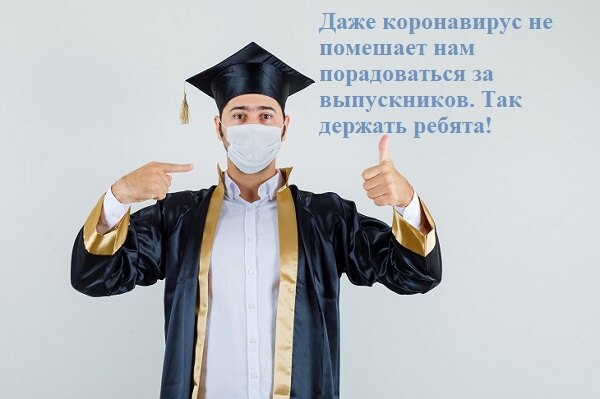 Учитель в маске показывает класс выпускникам